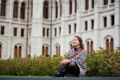 妇女坐草在宫殿议会,布达佩斯背景  免版税库存图片