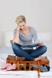 妇女坐被超载的手提箱,当读地图时 免版税库存图片