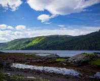 妇女坐调查距离的岩石在苏格兰 库存图片