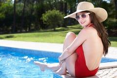 妇女坐边缘游泳在池 库存图片