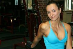 妇女坐长凳在健身房 图库摄影