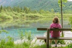 妇女坐长凳在湖附近在奥地利在阿尔卑斯附近 库存照片