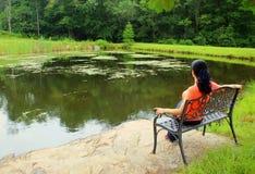 妇女坐长凳,在湖附近 免版税库存照片