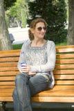 妇女坐长凳 免版税库存图片