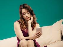 妇女坐长沙发使用手机 免版税库存图片