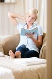 妇女坐长沙发读一本书 免版税图库摄影