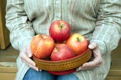 妇女坐门廊并且拿着有苹果接近的碗 库存图片