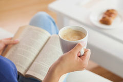 妇女坐读书的沙发拿着她的咖啡杯 免版税库存照片