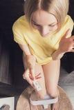 妇女坐洗手间并且举行一个正面妊娠试验 免版税库存图片