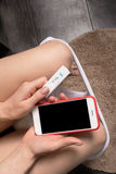 妇女坐洗手间并且拿着一个正面妊娠试验和手机 图库摄影