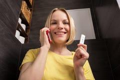 妇女坐洗手间并且拿着一个正面妊娠试验和手机 免版税图库摄影