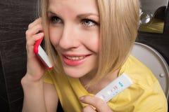 妇女坐洗手间并且拿着一个正面妊娠试验和手机 免版税库存照片