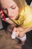 妇女坐洗手间并且拿着一个正面妊娠试验和手机 免版税库存图片