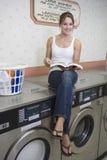 妇女坐洗衣机在自动洗衣店 库存图片