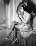 妇女坐从flacon的虚荣嗅到的香水(所有人被描述不更长生存,并且庄园不存在 供应商 免版税库存图片