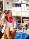 妇女坐bitt在小游艇船坞 库存图片