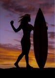妇女坚持冲浪板日落 免版税库存照片