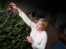 妇女垂悬的圣诞节装饰品 免版税库存照片