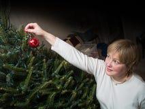 妇女垂悬的圣诞节装饰品 免版税库存图片