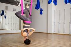 妇女垂悬颠倒做航空反重力瑜伽锻炼 免版税库存照片