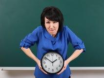妇女培养一块重的手表,摆在粉笔板、时间和教育概念,绿色背景,演播室射击 免版税库存图片