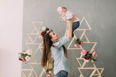 妇女培养微笑的婴孩在用花装饰的木粱的背景 图库摄影
