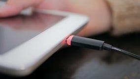 妇女塞住黑闪电充电的缆绳的` s手入片剂 库存图片