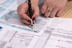 妇女填写报税表1040 免版税库存照片