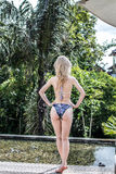 妇女夏天时尚 有适合身体的,长的腿,在比基尼泳装的健康皮肤愉快的性感的女孩,晒日光浴由游泳池  免版税库存照片