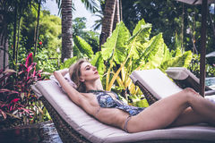 妇女夏天时尚 有适合身体的,长的腿,在比基尼泳装的健康皮肤愉快的性感的女孩,晒日光浴由游泳池  库存照片