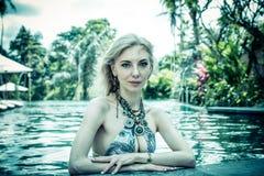 妇女夏天时尚 有适合身体的,长的腿,在比基尼泳装的健康皮肤愉快的性感的女孩,晒日光浴由游泳池  免版税图库摄影
