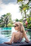 妇女夏天时尚 有适合身体的,长的腿,在比基尼泳装的健康皮肤愉快的性感的女孩,晒日光浴由游泳池  库存图片