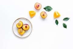 妇女夏天breackfast用桔子和桃子在白色背景舱内甲板位置大模型的板材结果实 免版税库存照片
