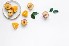 妇女夏天breackfast用桔子和桃子在白色背景舱内甲板位置大模型的板材结果实 免版税库存图片