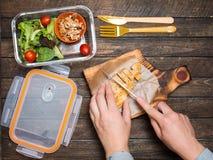 妇女外卖餐为她的孩子做准备 学校午餐箱子wi 免版税库存图片