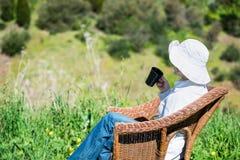 妇女外面坐与杯子的一条柳条长凳 免版税库存图片
