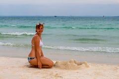 妇女大厦在海滩的沙子城堡 比基尼泳装的轻松的微笑的妇女 海滩天活动 免版税库存照片