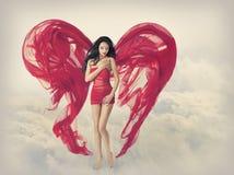 妇女天使飞过当织品布料,红色礼服的时装模特儿女孩心脏形状,飞行在天空云彩 图库摄影