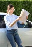 妇女失去的地图汽车旅行 库存图片