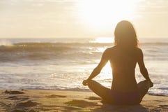 妇女女孩坐的日出日落比基尼泳装海滩 库存图片
