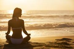 妇女女孩坐的日出日落比基尼泳装海滩 免版税图库摄影