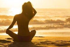 妇女女孩坐的日出日落比基尼泳装海滩 免版税库存图片