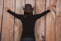 妇女女牛仔木墙壁后面传播 库存图片