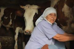 挤奶一头自创母牛的女性农夫在谷仓 免版税库存图片