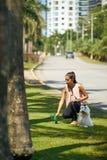 妇女她的法国狮子狗清洁粪便  免版税库存图片