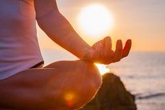 妇女实践坐在莲花姿势的瑜伽在日出 思考在日落的妇女剪影在海滩 免版税图库摄影