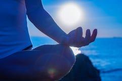 妇女实践坐在莲花姿势的瑜伽在日出 思考在海滩的妇女剪影 库存照片