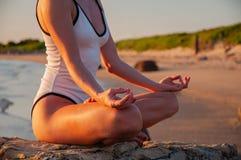 妇女实践坐在莲花姿势的瑜伽在日出 思考在海滩的妇女剪影 免版税库存照片