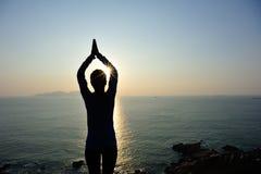 妇女实践瑜伽在日出海边 免版税图库摄影