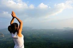 妇女实践瑜伽在日出海边 库存照片